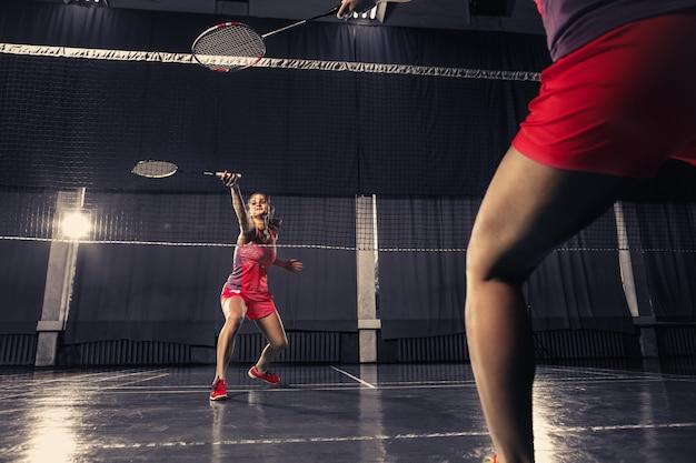 Jonge vrouw badminton spelen op sportschool Gratis Foto