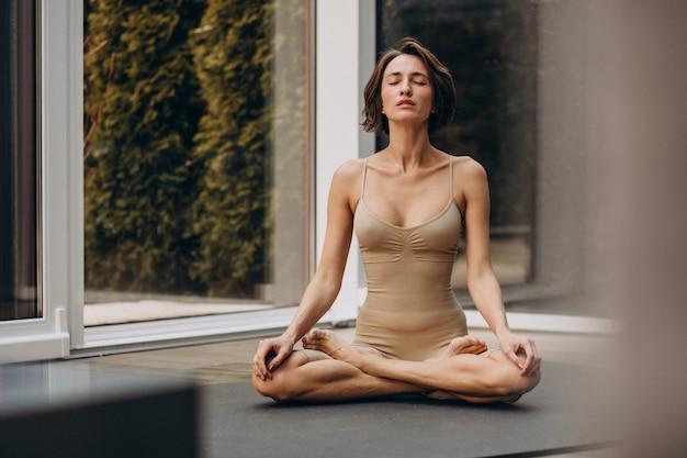 Jonge vrouw beoefenen van yoga thuis Gratis Foto