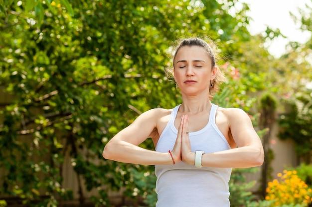 Jonge vrouw beoefent yoga in de tuin Premium Foto