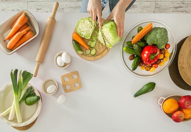 Jonge vrouw bereidt een salade in de keuken. Gratis Foto