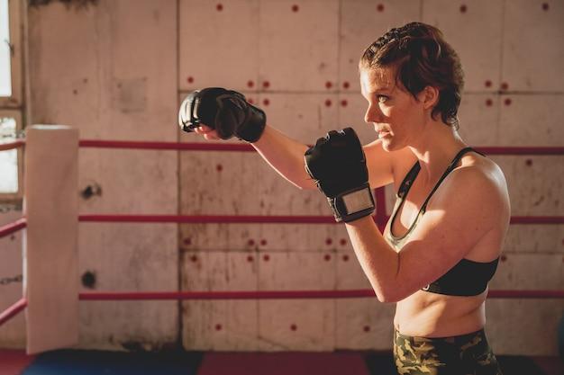 Jonge vrouw bereidt zich voor op wedstrijden mma in de kooi. training in een sporthal Premium Foto