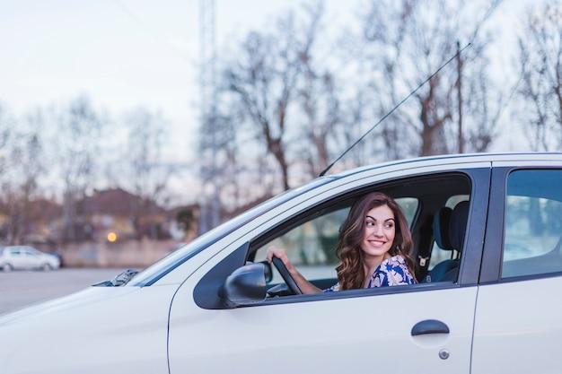 Jonge vrouw besturen van een auto in de stad. portret van een mooie vrouw in een auto, kijkt uit het raam en glimlacht. reizen en vakanties concepten Premium Foto