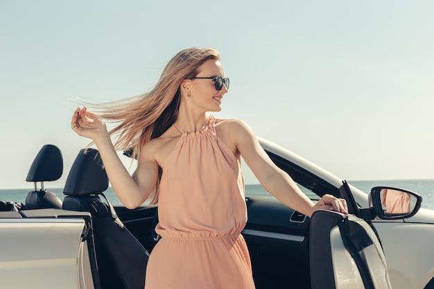 Jonge vrouw bestuurt een auto op het strand Premium Foto