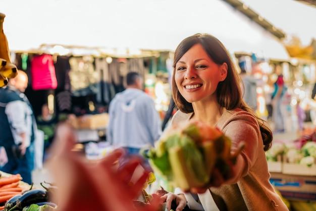 Jonge vrouw bij de markt die groenten kiest. Premium Foto