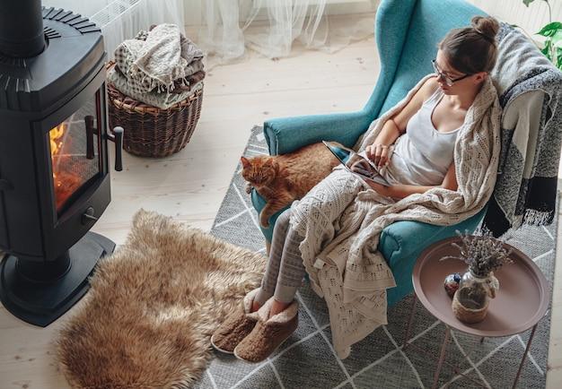 Jonge vrouw bij de open haard, zittend in een gezellige fauteuil, met een warme deken, met behulp van een tablet Premium Foto
