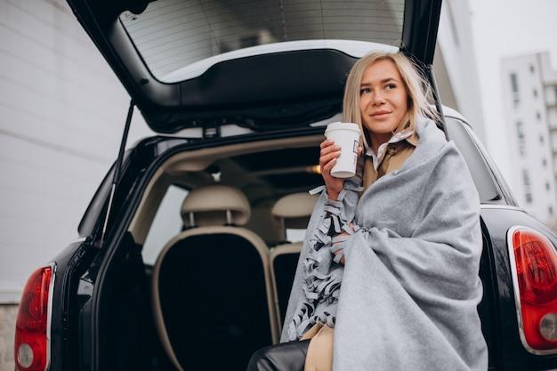 Jonge vrouw bij haar auto staan en koffie drinken Gratis Foto