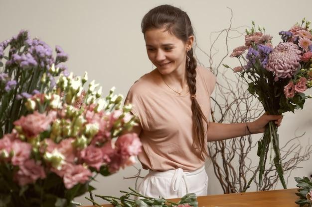 Jonge vrouw bloemist in haar studio een mooi boeket maken Premium Foto