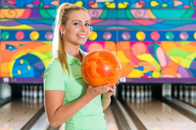 Jonge vrouw bowlen plezier Premium Foto