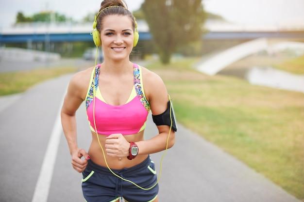 Jonge vrouw buiten uitoefenen. goed weer om te gaan joggen bij de rivier Gratis Foto