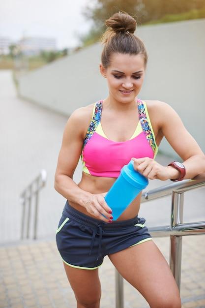 Jonge vrouw buiten uitoefenen. sportieve vrouw met een fles vol eiwitten Gratis Foto