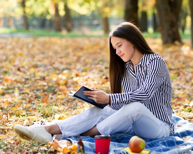 Jonge vrouw buitenshuis lezen Gratis Foto
