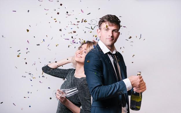 Jonge vrouw dichtbij man met fles drank tussen het werpen van confettien Gratis Foto