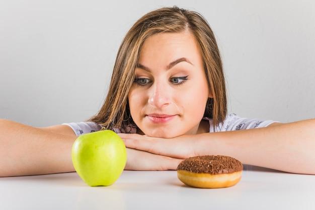 Jonge vrouw die aan appel in plaats van doughnut kiest te eten Gratis Foto