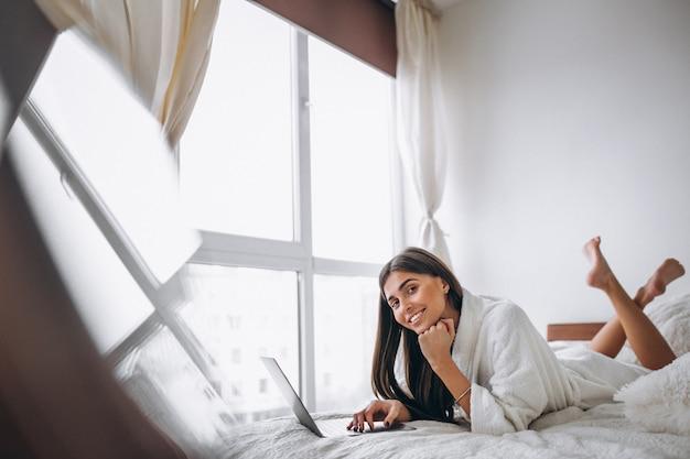 Jonge vrouw die aan computer in bed werkt Gratis Foto