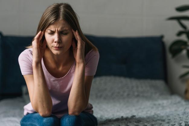 Jonge vrouw die aan hoofdpijnzitting op bed lijdt Gratis Foto