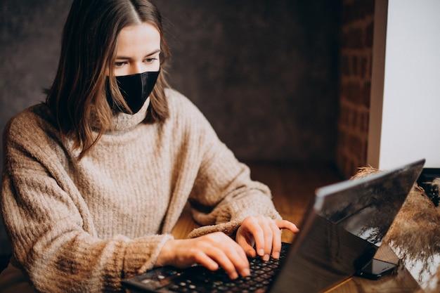 Jonge vrouw die aan laptop in een koffie werkt die masker draagt Gratis Foto