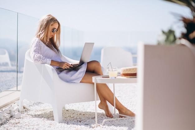 Jonge vrouw die aan laptop op een vakantie werkt Gratis Foto