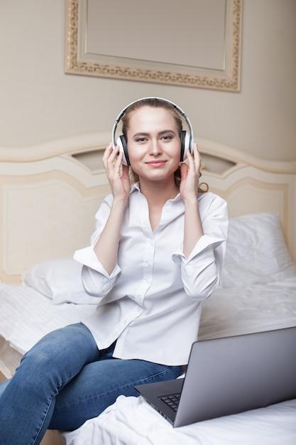 Jonge vrouw die aan muziek luistert en laptop op het bed met behulp van Premium Foto