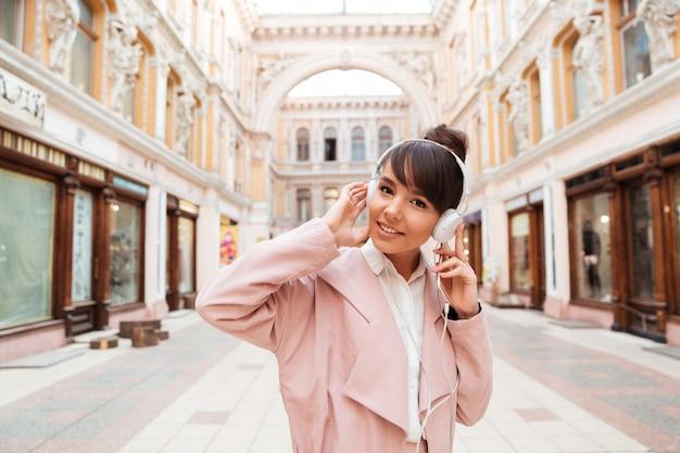 Jonge vrouw die aan muziek met hoofdtelefoons op een stadsstraat luistert Gratis Foto