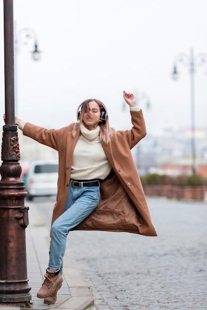 Jonge vrouw die aan muziek op hoofdtelefoons in de stad luistert Gratis Foto