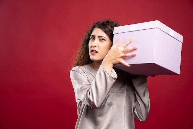Jonge vrouw die aan purpere giftdoos probeert te luisteren. Gratis Foto