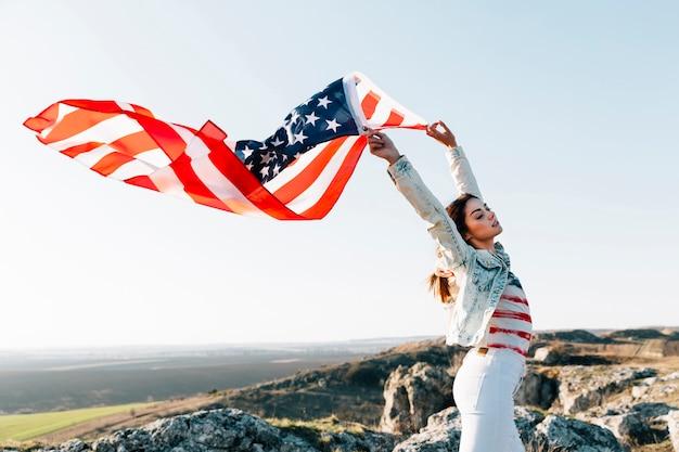 Jonge vrouw die amerikaanse vlag bovenop berg houdt Gratis Foto