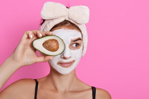 Jonge vrouw die avocado in handen houdt en haar ogen bedekt met fruit, met wit masker op gezicht, opzij kijkt, hoofdband met boog draagt die over roze achtergrond wordt geïsoleerd. Gratis Foto