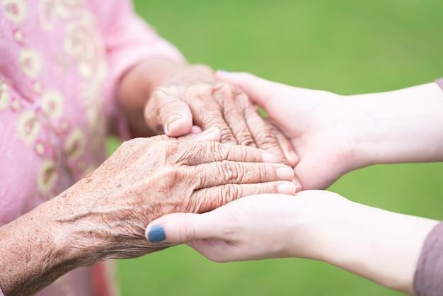 Jonge vrouw die bejaarde hand houdt Premium Foto