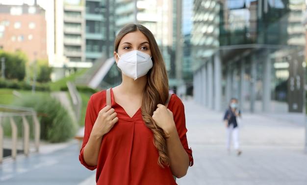 Jonge vrouw die beschermend masker kn95 ffp2 draagt die in moderne stadsstraat loopt. Premium Foto