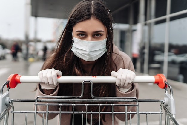 Jonge vrouw die beschermingsgezichtsmasker draagt tegen coronavirus 2019-ncov die een boodschappenwagentje duwt. Gratis Foto