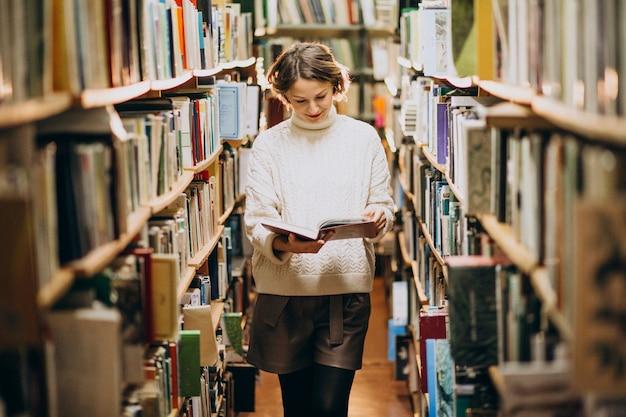Jonge vrouw die bij de bibliotheek bestudeert Gratis Foto
