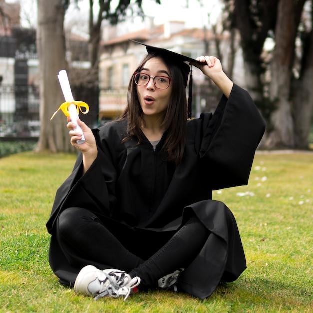 Jonge vrouw die bij graduatieceremonie haar glb houdt Gratis Foto