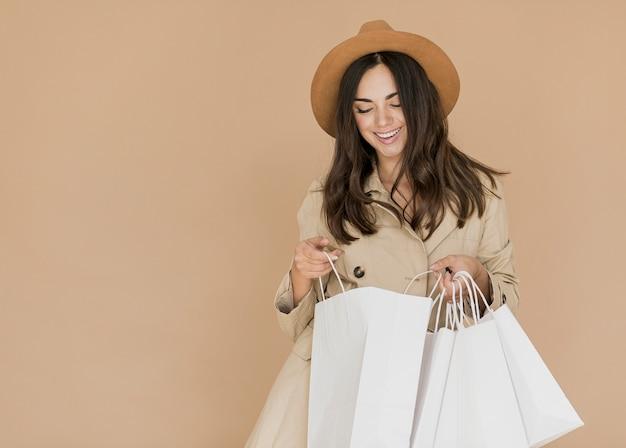 Jonge vrouw die binnen het winkelen zakken kijkt Gratis Foto