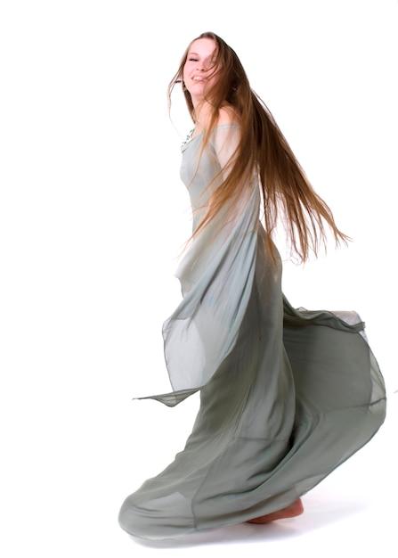 Jonge vrouw die binnen tegen witte achtergrond danst Premium Foto