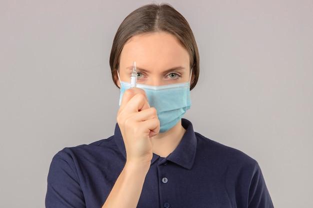 Jonge vrouw die blauw poloshirt in beschermend medisch masker draagt dat een ampul met een vaccin houdt dat camera met ernstig gezicht bekijkt dat zich op geïsoleerde grijze achtergrond bevindt Gratis Foto