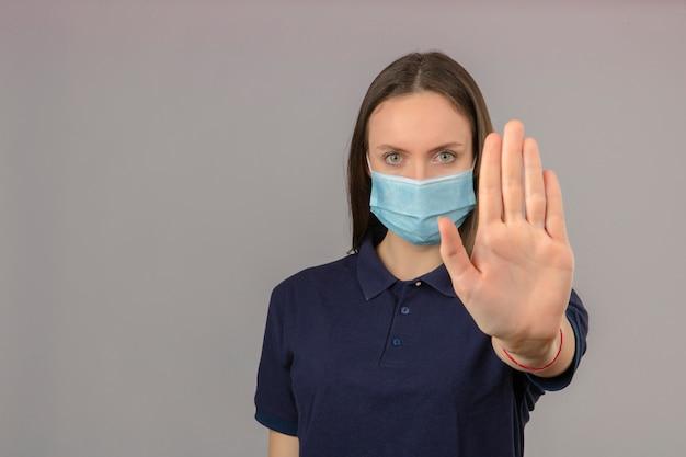Jonge vrouw die blauw poloshirt in beschermend medisch masker draagt dat het gebaar van het handeinde met ernstig die gezicht toont op lichtgrijze achtergrond met exemplaarruimte wordt geïsoleerd Gratis Foto