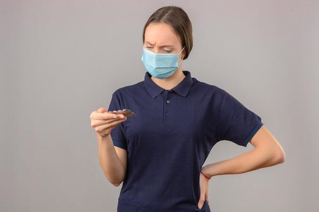 Jonge vrouw die blauw poloshirt in beschermende medische de blaarpillen van de maskerholding in hand dragen bekijkend pillen met ernstig gezicht die zich op lichtgrijze achtergrond bevinden Gratis Foto