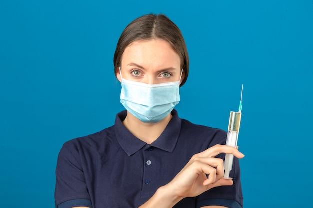 Jonge vrouw die blauw poloshirt in de beschermende medische spuit dragen die van de maskerholding camera met ernstig gezicht bekijken die zich op geïsoleerde blauwe achtergrond bevinden Gratis Foto