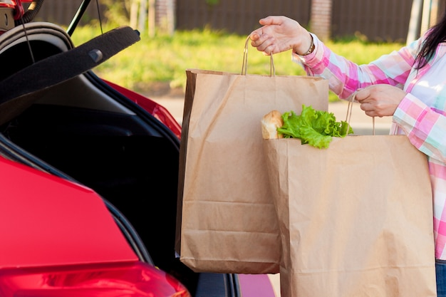 Jonge vrouw die boodschappen van een supermarkt in papieren zakken zet in de kofferbak van een auto. Premium Foto