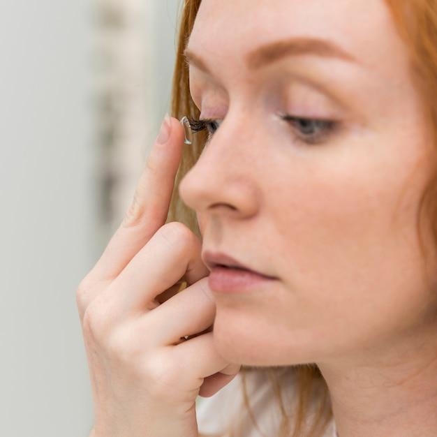 Jonge vrouw die contactlens in haar oog zet Gratis Foto