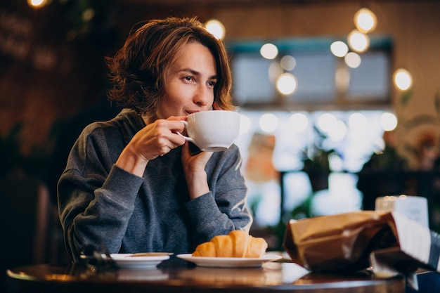 Jonge vrouw die croissants eet in een koffie Gratis Foto