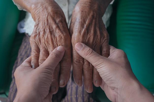 Jonge vrouw die de hand van een bejaarde houdt. Gratis Foto