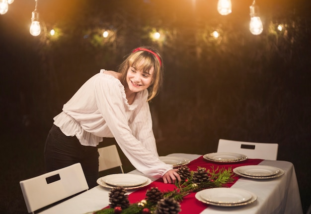Jonge vrouw die de lijst voor kerstmisdiner plaatst Gratis Foto