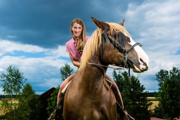 Jonge vrouw die de paarden berijdt op de weide Premium Foto