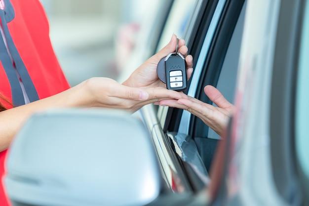 Jonge vrouw die de sleutels van haar nieuwe auto ontvangt, concentreert zich op sleutel. Premium Foto