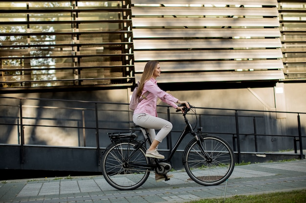 Jonge vrouw die e-fiets berijden in stedelijk milieu Premium Foto