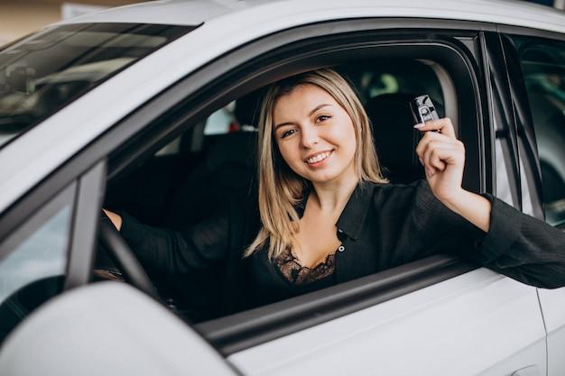 Jonge vrouw die een auto in een autotoonzaal test Gratis Foto