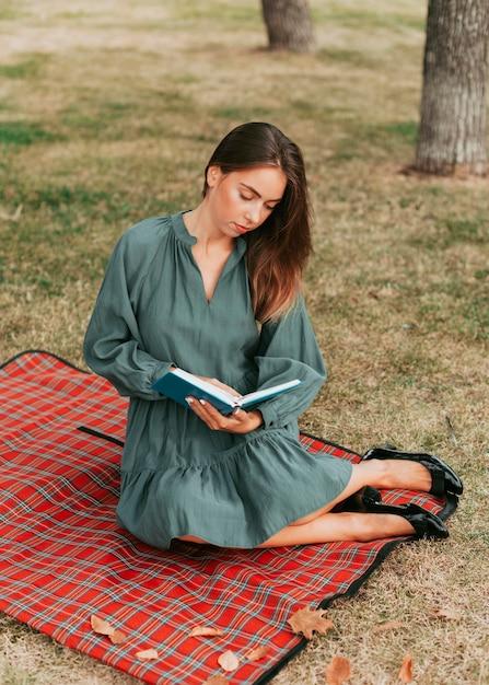Jonge vrouw die een boek op een picknickkleed leest Premium Foto