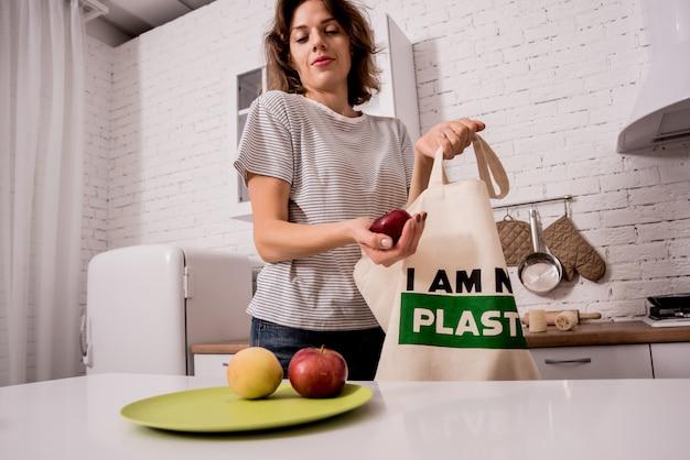 Jonge vrouw die een doekzak houdt. bij de keuken. ik ben geen plastic. campagne om het gebruik van plastic zakken te verminderen. zero waste Premium Foto