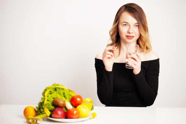 Jonge vrouw die een glas water en een pil voor gewichtsverlies houdt Premium Foto